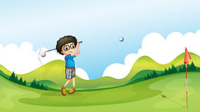 A boy playing golf at the field Royalty Free Stock Photos