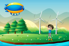 A boy playing golf in the field with windmills Stock Images