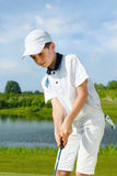 Boy playing golf. And hitting by putter on green stock images