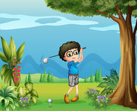 A boy playing golf near the tree Stock Photography