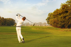 Boy playing golf. Boy golf player hitting by iron from fairway at autumn evening Stock Photo