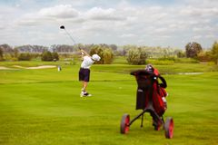 Boy playing golf. Boy golf player hitting by iron from fairway at golf course Stock Image