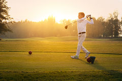 Boy playing golf. Boy golf player hitting by iron from fairway at sunset Stock Photo