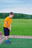 Boy playing golf in the summer Royalty Free Stock Photo
