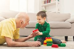 Boy playing with grandfather in building kit. Little happy boy playing with his grandfather in colorful children`s building kit, sitting on floor at home, copy stock photography