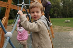 Boy in a playing ground. Climbing up by the rope net Royalty Free Stock Photo