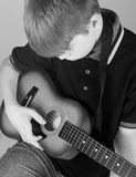 Boy Playing Guitar. Teach kids music!  This boy is learning how to play guitar Royalty Free Stock Images