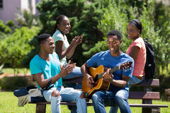 Boy playing guitar. Cheerful african college boy playing guitar for friends Stock Photography