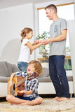 Boy playing guitar and father and sister dancing Royalty Free Stock Image