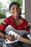 Boy Playing Guitar In Garage Stock Photography