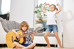 Boy playing guitar and girl dancing at home Stock Photography