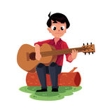 Boy playing guitar sitting on a log, camping, hiking concept Royalty Free Stock Image