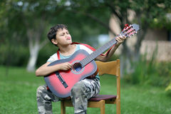 Boy playing the guitar very passionary outdoors Stock Images