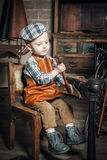 Boy playing with hammer and shoe. Retro shot of a little boy hammering and imitating the cobbler Stock Photography