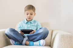 Boy playing hand-held video game on sofa Royalty Free Stock Images