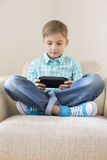 Boy playing hand-held video game on sofa at home Stock Images