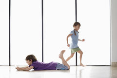 Boy Playing Handheld Video Game While Sister Running Around Stock Photography