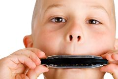 Boy playing harmonica. A young boy playing music on his harmonica Stock Photography