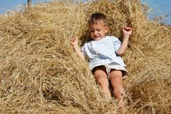 Boy playing in hay Stock Image