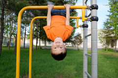 Boy playing with head down outdoors on horizontal bar gym. Kid on playground, children activity. Active healthy Royalty Free Stock Image