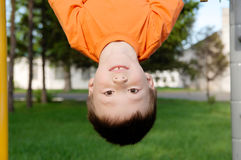 Boy playing with head down outdoors on horizontal bar gym. Kid on playground, children activity. Child having fun. Active healthy Stock Photos