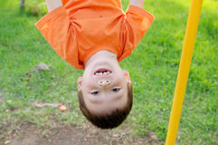 Boy playing with head down outdoors on horizontal bar gym. Kid on playground, children activity. Child having fun. Active healthy Stock Images