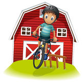 A boy playing with his bike in front of the barnhouse Royalty Free Stock Image