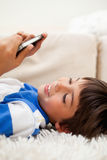 Boy playing with his cellphone while lying on the carpet Stock Photo