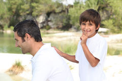 Boy playing with his dad Stock Images
