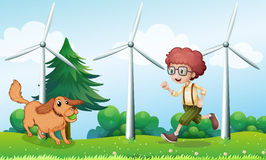 A boy playing with his dog near the windmill Royalty Free Stock Photography