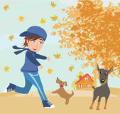 Boy playing with his dogs in autumn Stock Image