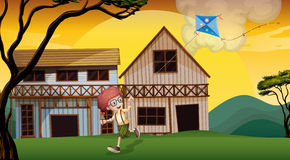 A boy playing with his kite in front of the wooden barnhouses Royalty Free Stock Images