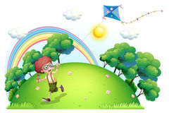 A boy playing with his kite at the hilltop Royalty Free Stock Photography
