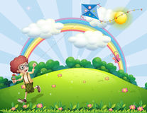 A boy playing with his kite at the hilltop with a rainbow Stock Images