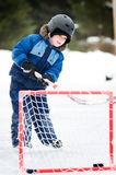 Boy playing hockey. Young boy playing ice hockey on an outdoor rink Stock Image