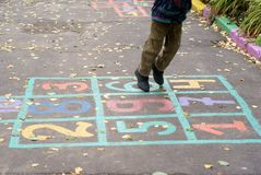 Boy playing hopscotch game. In the autumn Royalty Free Stock Image