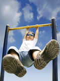 Boy playing on horizontal bar Stock Image