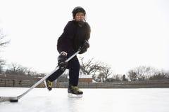 Boy playing ice hockey. Boy in ice hockey uniform skating on ice rink moving puck Royalty Free Stock Photos