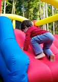 Boy playing on inflatable castle Stock Photography