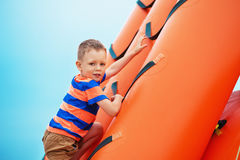 Boy playing on an inflatable playground on the beach on a summer Stock Photo