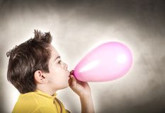 Boy playing inflating a balloon. Little boy playing inflating a balloon Royalty Free Stock Photography