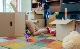Boy playing inside a moving box while his father unpacks. Little boy playing inside a moving box while his father unpacks in the living room royalty free stock images
