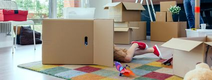 Boy playing inside a moving box while his father unpacks. Little boy playing inside a moving box while his father unpacks in the living room royalty free stock photo