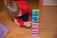 Boy playing Jenga game stock photo