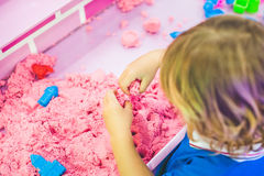 Boy playing with kinetic sand in preschool. The development of fine motor concept. Creativity Game concept Stock Photos