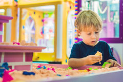 Boy playing with kinetic sand in preschool. The development of fine motor concept. Creativity Game concept Royalty Free Stock Photo