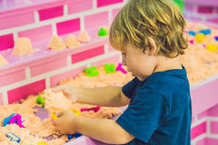 Boy playing with kinetic sand in preschool. The development of fine motor concept. Creativity Game concept Royalty Free Stock Images