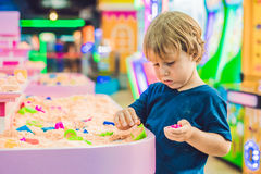 Boy playing with kinetic sand in preschool. The development of fine motor concept. Creativity Game concept Stock Photo