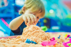 Boy playing with kinetic sand in preschool. The development of fine motor concept. Creativity Game concept Royalty Free Stock Image