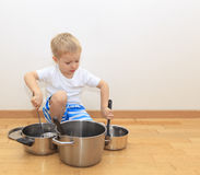 Boy playing with kitchen utensils Royalty Free Stock Photography